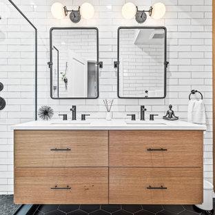 На фото: главная ванная комната среднего размера в современном стиле с плоскими фасадами, фасадами цвета дерева среднего тона, душевой комнатой, унитазом-моноблоком, белой плиткой, белыми стенами, врезной раковиной, столешницей из искусственного кварца, черным полом, душем с распашными дверями, белой столешницей, тумбой под две раковины и встроенной тумбой с