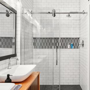 Diseño de cuarto de baño contemporáneo, de tamaño medio, con armarios con paneles lisos, puertas de armario de madera oscura, ducha esquinera, baldosas y/o azulejos blancas y negros, baldosas y/o azulejos blancos, baldosas y/o azulejos de cemento, paredes blancas, lavabo sobreencimera, encimera de madera, suelo multicolor, ducha con puerta corredera y encimeras marrones