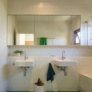 Kleines Mid-Century Kinderbad mit Einbaubadewanne, Duschbadewanne, weißen Fliesen, Keramikfliesen, weißer Wandfarbe, Keramikboden, Wandwaschbecken, gefliestem Waschtisch, grünem Boden, Duschvorhang-Duschabtrennung und weißer Waschtischplatte in Townsville