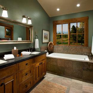 Ejemplo de cuarto de baño rural con lavabo bajoencimera, armarios con paneles empotrados, puertas de armario de madera oscura, bañera encastrada, baldosas y/o azulejos marrones, paredes verdes y baldosas y/o azulejos de pizarra