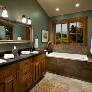 Immagine di una stanza da bagno stile rurale con lavabo sottopiano, ante con riquadro incassato, ante in legno scuro, vasca da incasso, piastrelle marroni, pareti verdi e piastrelle in ardesia