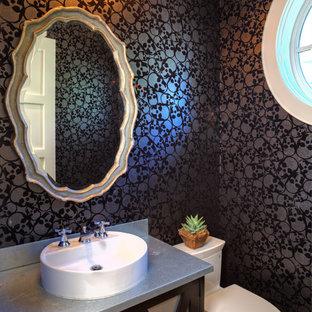 Diseño de cuarto de baño tradicional renovado, pequeño, con lavabo sobreencimera, encimera de zinc, sanitario de una pieza, armarios tipo mueble, puertas de armario de madera en tonos medios, paredes negras y suelo de madera en tonos medios