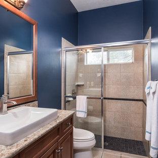 Ejemplo de cuarto de baño de estilo americano, de tamaño medio, con armarios con rebordes decorativos, puertas de armario de madera oscura, baldosas y/o azulejos marrones, baldosas y/o azulejos de travertino, lavabo sobreencimera, encimera de granito y encimeras marrones