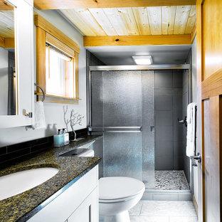 Immagine di una piccola stanza da bagno con doccia american style con lavabo sottopiano, ante in stile shaker, ante bianche, top in quarzo composito, doccia alcova, WC monopezzo, piastrelle nere, piastrelle di vetro, pareti grigie e pavimento in gres porcellanato