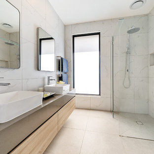 This is an example of a mid-sized contemporary master bathroom in Melbourne with furniture-like cabinets, light wood cabinets, a freestanding tub, a corner shower, a one-piece toilet, white tile, ceramic tile, white walls, ceramic floors, engineered quartz benchtops, grey floor, an open shower and grey benchtops.