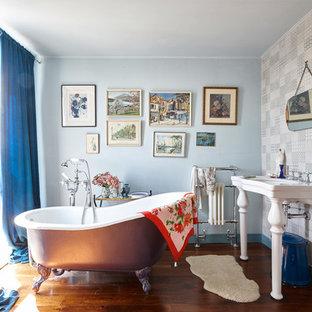 Klassisk inredning av ett mellanstort en-suite badrum, med ett badkar med tassar, flerfärgade väggar, mörkt trägolv och ett konsol handfat