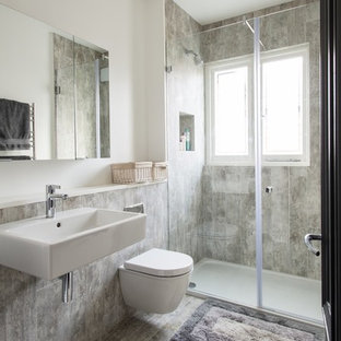 Inspiration for a medium sized contemporary shower room bathroom in London with a wall mounted toilet, a wall-mounted sink, grey floors, an alcove shower, grey tiles and white walls.