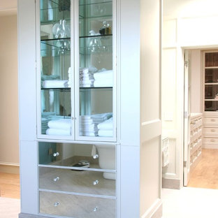 Example of a transitional bathroom design in Los Angeles with glass-front cabinets