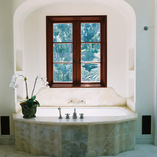 Tuscan stone slab and beige tile bathroom photo in Los Angeles with an undermount tub