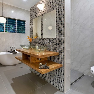 Inspiration for a mid-sized contemporary master bathroom in Cairns with open cabinets, light wood cabinets, a freestanding tub, a two-piece toilet, gray tile, multi-coloured tile, grey walls, a vessel sink, wood benchtops and grey floor.