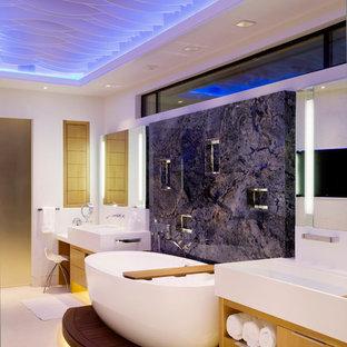 Immagine di una grande stanza da bagno padronale minimal con ante lisce, ante in legno chiaro, vasca freestanding, lastra di pietra, pareti blu, lavabo rettangolare, pavimento in gres porcellanato e top in superficie solida