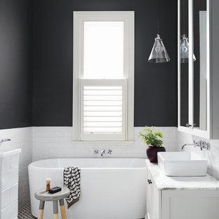 Cette image montre une salle de bain design de taille moyenne avec des portes de placard blanches, une baignoire indépendante et un carrelage noir et blanc.