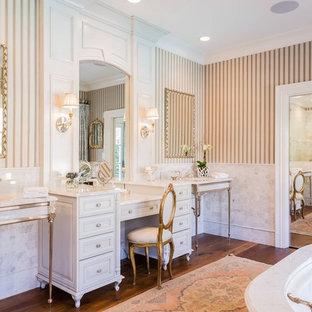 Klassisk inredning av ett stort en-suite badrum, med ett fristående badkar, en hörndusch, mellanmörkt trägolv, ett undermonterad handfat och marmorbänkskiva