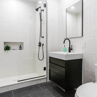 Alcove shower - mid-sized modern white tile and porcelain tile porcelain floor and gray floor alcove shower idea in New York with flat-panel cabinets, black cabinets, a one-piece toilet, white walls, an integrated sink, solid surface countertops, a hinged shower door and white countertops