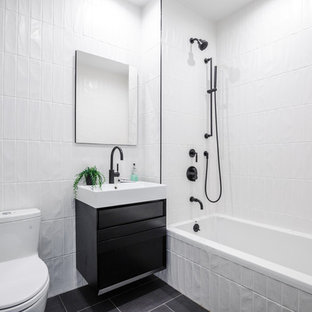 Mid-sized minimalist white tile and porcelain tile porcelain floor and gray floor drop-in bathtub photo in New York with flat-panel cabinets, black cabinets, a one-piece toilet, white walls, an integrated sink, solid surface countertops and white countertops