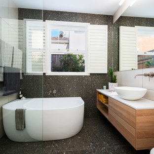 Photo of a mid-sized contemporary master bathroom in Melbourne with furniture-like cabinets, medium wood cabinets, a freestanding tub, an open shower, a wall-mount toilet, pink tile, ceramic tile, multi-coloured walls, ceramic floors, a vessel sink, granite benchtops, grey floor, an open shower, white benchtops, a single vanity and a floating vanity.
