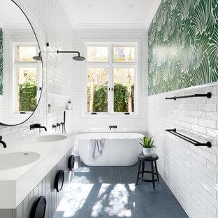 Immagine di una stanza da bagno nordica con ante beige, vasca/doccia, piastrelle bianche, pareti multicolore, lavabo integrato, pavimento grigio, doccia aperta e top bianco