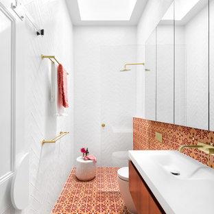 Modelo de cuarto de baño con ducha, nórdico, con armarios con paneles lisos, puertas de armario de madera oscura, ducha a ras de suelo, baldosas y/o azulejos naranja, baldosas y/o azulejos rojos, baldosas y/o azulejos blancos, lavabo integrado, suelo multicolor, ducha abierta y encimeras blancas