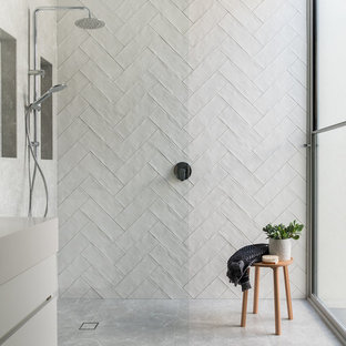 Inspiration for a contemporary bathroom in Melbourne with flat-panel cabinets, white cabinets, a curbless shower, white tile, white walls, grey floor, an open shower and white benchtops.