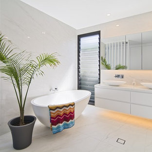 This is an example of a contemporary bathroom in Melbourne with flat-panel cabinets, white cabinets, a freestanding tub, white walls and a vessel sink.