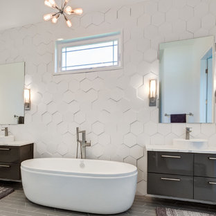 Design ideas for a contemporary bathroom in Cleveland with flat-panel cabinets, black cabinets, a freestanding bath, white tiles, white walls, a vessel sink and black floors.