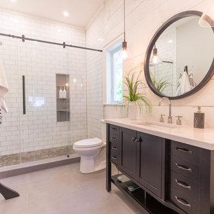 Immagine di una grande stanza da bagno contemporanea con ante a filo, ante nere, WC monopezzo, piastrelle bianche, pareti bianche, pavimento in cemento, lavabo da incasso, top in superficie solida, pavimento grigio e top bianco
