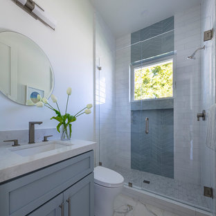 Alcove shower - small country kids' white tile and ceramic tile porcelain floor and white floor alcove shower idea in San Francisco with shaker cabinets, gray cabinets, a one-piece toilet, white walls, an undermount sink, quartz countertops, a hinged shower door and white countertops