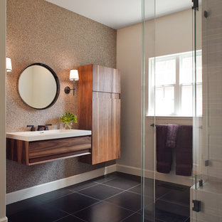 Example of a mid-sized trendy gray tile ceramic tile and brown floor corner shower design in San Francisco with a wall-mount sink, flat-panel cabinets, dark wood cabinets, a hinged shower door and beige walls