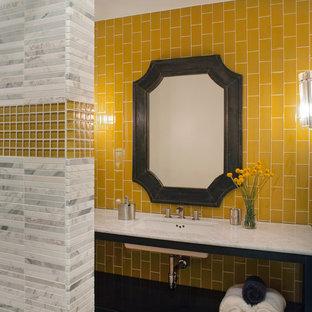 Стильный дизайн: ванная комната в современном стиле с мраморной столешницей, плиткой мозаикой, желтыми стенами, желтой плиткой, черными фасадами и врезной раковиной - последний тренд