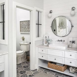 Lantlig inredning av ett vit vitt en-suite badrum, med skåp i shakerstil, vita skåp, en toalettstol med separat cisternkåpa, vita väggar, cementgolv, ett fristående handfat och flerfärgat golv