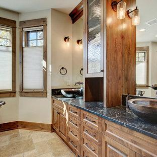 Foto på ett rustikt en-suite badrum, med luckor med upphöjd panel, skåp i mellenmörkt trä, ett fristående badkar, en dusch i en alkov, beige kakel, keramikplattor, vita väggar, travertin golv, ett fristående handfat och bänkskiva i täljsten