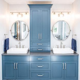 Diseño de cuarto de baño principal, actual, de tamaño medio, con armarios estilo shaker, puertas de armario azules, bañera exenta, ducha a ras de suelo, sanitario de una pieza, paredes blancas, suelo de baldosas de porcelana, lavabo sobreencimera, encimera de esteatita, suelo blanco, ducha con puerta con bisagras y encimeras grises