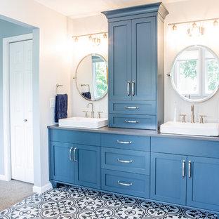 Modelo de cuarto de baño principal, contemporáneo, de tamaño medio, con armarios estilo shaker, puertas de armario azules, bañera exenta, ducha a ras de suelo, sanitario de una pieza, paredes blancas, suelo de baldosas de porcelana, lavabo sobreencimera, encimera de esteatita, suelo blanco, ducha con puerta con bisagras y encimeras grises