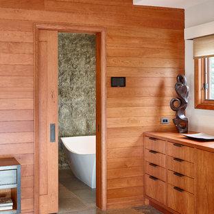 Idee per una grande stanza da bagno padronale moderna con ante lisce, ante in legno scuro, piastrelle grigie, lastra di pietra, pareti grigie, lavabo integrato, vasca freestanding, pavimento in cemento e top in legno