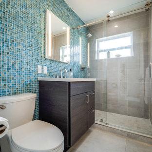 Foto de cuarto de baño con ducha, minimalista, de tamaño medio, con armarios con paneles lisos, puertas de armario de madera en tonos medios, ducha empotrada, sanitario de una pieza, baldosas y/o azulejos azules, baldosas y/o azulejos de vidrio laminado, paredes grises, suelo de baldosas de porcelana, lavabo bajoencimera, encimera de cuarzo compacto, suelo gris, ducha con puerta corredera y encimeras grises