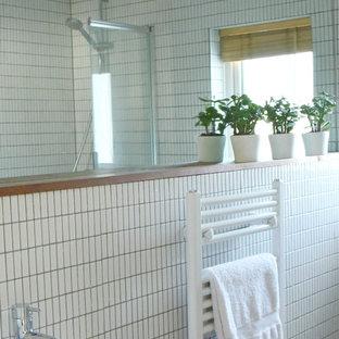 Foto di una piccola stanza da bagno per bambini con ante lisce, ante bianche, vasca da incasso, vasca/doccia, WC a due pezzi, piastrelle bianche, piastrelle a mosaico, pareti bianche, pavimento in sughero e lavabo sospeso