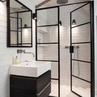 Bild på ett funkis badrum med dusch, med släta luckor, svarta skåp, en dusch i en alkov, en vägghängd toalettstol, tunnelbanekakel, vita väggar, mosaikgolv, ett fristående handfat, träbänkskiva och dusch med gångjärnsdörr
