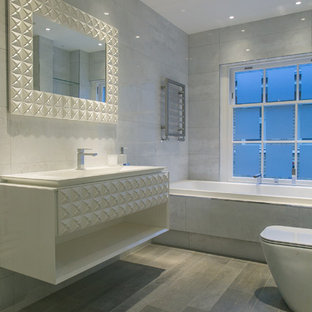 This is an example of a medium sized contemporary ensuite bathroom in London with engineered stone worktops, a built-in bath, grey tiles, porcelain tiles, white walls and porcelain flooring.