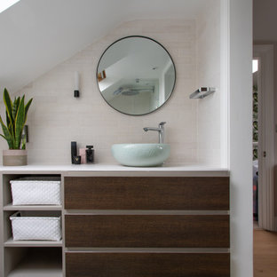 Photo of a small contemporary ensuite bathroom in London with flat-panel cabinets, dark wood cabinets, a corner shower, beige tiles, porcelain tiles, solid surface worktops, an open shower, white worktops, a single sink and a built in vanity unit.
