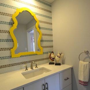 Immagine di una grande stanza da bagno per bambini minimal con ante lisce, ante bianche, vasca ad alcova, vasca/doccia, WC monopezzo, piastrelle multicolore, piastrelle di vetro, pareti grigie, lavabo sottopiano e top in quarzo composito