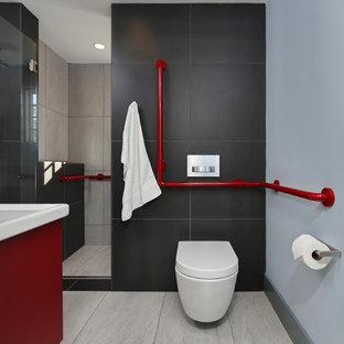 Esempio di una piccola stanza da bagno padronale moderna con lavabo sospeso, ante lisce, ante rosse, WC sospeso, piastrelle nere, piastrelle in gres porcellanato, pareti nere e pavimento in gres porcellanato