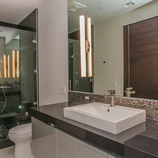 ロサンゼルスの中サイズのコンテンポラリースタイルのおしゃれなマスターバスルーム (フラットパネル扉のキャビネット、グレーのキャビネット、アルコーブ型シャワー、一体型トイレ、メタルタイル、白い壁、磁器タイルの床、ベッセル式洗面器、珪岩の洗面台) の写真