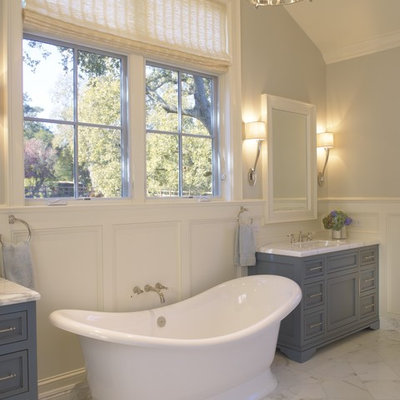 Example of a classic freestanding bathtub design in San Francisco with blue cabinets