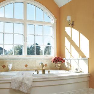 Diseño de cuarto de baño principal, moderno, grande, con bañera esquinera, parades naranjas, baldosas y/o azulejos beige y baldosas y/o azulejos de terracota