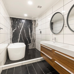 Inspiration for a large contemporary master black and white tile black floor and double-sink bathroom remodel in Phoenix with flat-panel cabinets, medium tone wood cabinets, an integrated sink, white countertops and a floating vanity