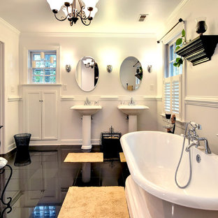Freestanding bathtub - traditional black floor freestanding bathtub idea in Other with a pedestal sink and white walls