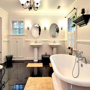 Klassisches Badezimmer mit Sockelwaschbecken, freistehender Badewanne, weißer Wandfarbe und schwarzem Boden in Sonstige