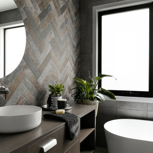 Mid-sized contemporary master bathroom in Melbourne with flat-panel cabinets, medium wood cabinets, a freestanding tub, brown tile, gray tile, a vessel sink, wood benchtops, grey floor, brown benchtops, a single vanity and a freestanding vanity.