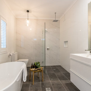 Design ideas for a traditional 3/4 wet room bathroom in Brisbane with flat-panel cabinets, white cabinets, a freestanding tub, a two-piece toilet, white tile, an integrated sink, grey floor, an open shower and white benchtops.