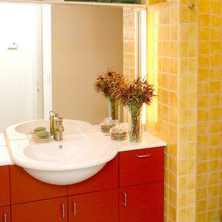 Immagine di una stanza da bagno minimal con lavabo sospeso, ante lisce, ante rosse, top in superficie solida, doccia ad angolo, piastrelle gialle, piastrelle in gres porcellanato, pareti bianche e pavimento in gres porcellanato